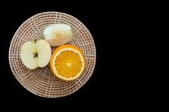 manzana y naranja cortadas en la placa de madera imagenes de archivo