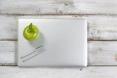 Manzana y ordenador portátil verdes frescos encima de la mesa vieja fotos de archivo