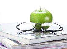 Manzana y vidrios verdes en cierre de la pila de la revista y de libro para arriba Foto de archivo