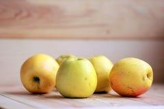 Manzanas amarillas en el piso de madera Imagenes de archivo