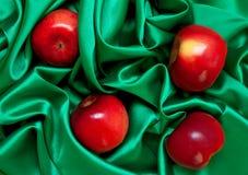 Manzanas brillantes en el satén verde vibrante Fotos de archivo libres de regalías