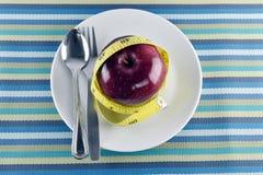 Manzanas, cinta métrica y platos y cubiertos rojos en plato en mantelería Fotos de archivo