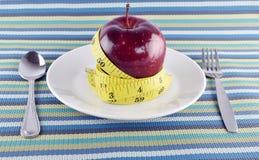 Manzanas, cinta métrica y platos y cubiertos rojos en plato en mantelería Imagen de archivo libre de regalías