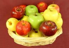 Manzanas clasificadas en cesta en fondo rojo. Fotos de archivo