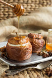 Manzanas cocidas rellenas con frutos secos, las nueces y el requesón, miel, canela primer, horizontal Fotos de archivo