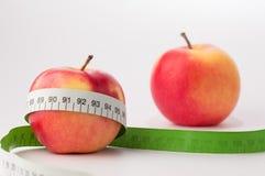 Manzanas con la cinta de la medida Imagenes de archivo