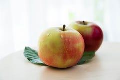 Manzanas con las hojas verdes aisladas en fondo ligero Imagen de archivo libre de regalías