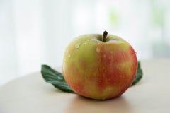 Manzanas con las hojas verdes en fondo ligero Foto de archivo libre de regalías