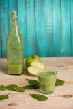 Manzanas con las hojas y el smoothie verdes en vidrio y botella Foto de archivo