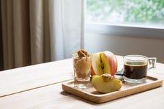 Manzanas con mantequilla de cacahuete y café sólo foto de archivo