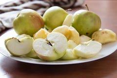 Manzanas cortadas en una placa blanca Foto de archivo libre de regalías