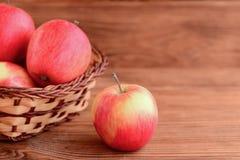 Manzanas crudas frescas en una tabla de madera y en una cesta Fondo de madera con el espacio de la copia para el texto Foto dulce Imágenes de archivo libres de regalías