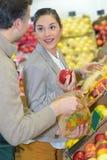 Manzanas de compra de la mujer que hablan con el tendero Imágenes de archivo libres de regalías