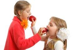 Manzanas de la mordedura de las muchachas Imagenes de archivo