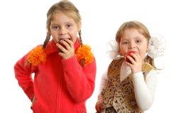 Manzanas de la mordedura de las muchachas en blanco Foto de archivo libre de regalías