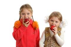 Manzanas de la mordedura de las muchachas en blanco Foto de archivo