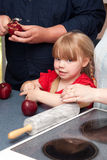 Manzanas de la peladura de la chica joven en cocina imagen de archivo libre de regalías