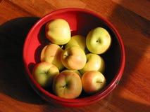 Manzanas de oro en el tazón de fuente de cerámica rojo, visión superior fotografía de archivo