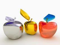 Manzanas del oro, de la plata y del vidrio en una placa de plata Imagenes de archivo