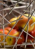 Manzanas detrás de las barras de metal plateado Fotos de archivo
