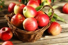 Manzanas en cesta en fondo de madera marrón Imagen de archivo