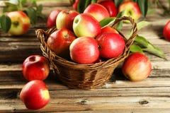 Manzanas en cesta en fondo de madera marrón Foto de archivo libre de regalías