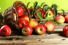 Manzanas en cesta en fondo de madera marrón Fotos de archivo
