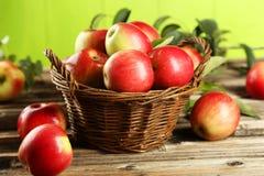 Manzanas en cesta en fondo de madera marrón Foto de archivo