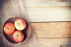 Manzanas en cesta en la tabla de madera Fotografía de archivo libre de regalías