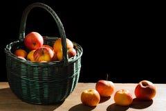 Manzanas en cesta en tablón viejo Imagen de archivo libre de regalías
