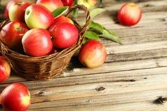 Manzanas en cesta en un fondo de madera marrón Fotos de archivo libres de regalías