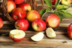 Manzanas en cesta en un fondo de madera marrón Fotos de archivo