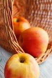 Manzanas en cesta en una tabla de madera Imagenes de archivo