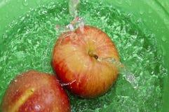 Manzanas en chapoteo del agua Foto de archivo libre de regalías