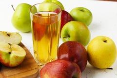 Manzanas en la tabla y un vidrio de zumo de manzana fotos de archivo
