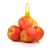 Manzanas en Mesh Sack plástico en el fondo blanco Fotos de archivo libres de regalías