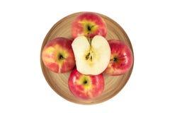 Manzanas en placa de madera en un fondo blanco Imagen de archivo