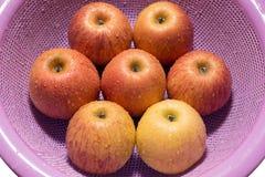 Manzanas en un cuenco neto purpúreo claro lavado Foto de archivo