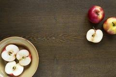 Manzanas en un plato de la arcilla en el tablero de madera Imagen de archivo libre de regalías