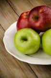 Manzanas en una placa blanca de cerámica Fotografía de archivo