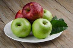 Manzanas en una placa blanca de cerámica Fotos de archivo