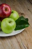 Manzanas en una placa blanca de cerámica Imagen de archivo libre de regalías