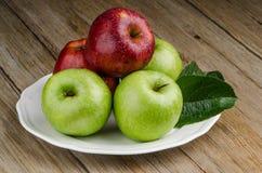 Manzanas en una placa blanca de cerámica Fotografía de archivo libre de regalías