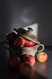 Manzanas frescas en el pote de arcilla en la sombra del sol Fotos de archivo