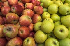 Manzanas frescas: a la izquierda son las manzanas anaranjadas con cortes, a la derecha son montaña de manzanas amarillas Fotos de archivo