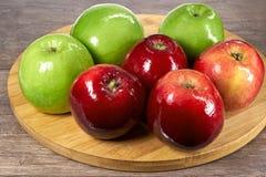Manzanas frescas, rojas y verdes en un tablero de madera Imagenes de archivo