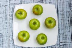 Manzanas frescas verdes en una placa blanca Fotografía de archivo