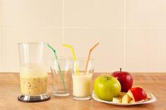 Manzanas frescas y vidrios del batido de leche en la tabla de cocina Imagen de archivo