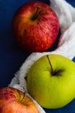 Manzanas 'golden delicious' y reales de la gala con un paño blanco contra un fondo azul Ciérrese para arriba, foco selectivo Imagenes de archivo