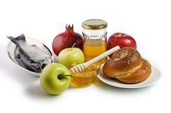 Manzanas, granadas, pescados, jalá y miel Imágenes de archivo libres de regalías
